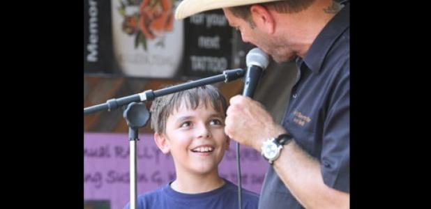 Tackle football player, Arin Stack, 10, takes an opportunity to thank people for their donations to help save tackle football as Dave McBride, owner of Dave's Sports Bar and Grill, holds an auction during a benefit to raise funds for the program.