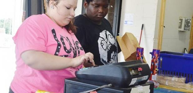 Megan Hunt totals a customer's purchases while John Williams bags them at Mr. W's Fireworks west of Copperas Cove.