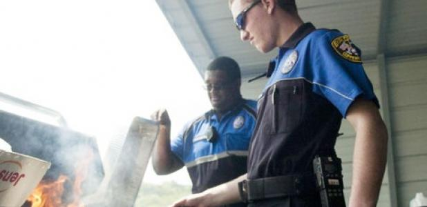 Copperas Cove senior Shawn Noorlun mans the grill as Police Explorers Tyrell Washington and Jason Stanley prepare hamburgers during the cookout funds raiser Saturday at Just Glocks.