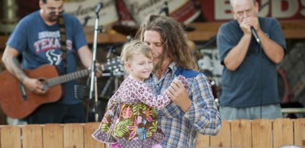 James Wright dances with his daughter Magnolia to the sounds of Justin Bravo & the Kind during a benefit for Texas Angel Tattoos and Rocky Hughes. Wright played with Rust Bucketz and Elution as five bands preformed on the night.