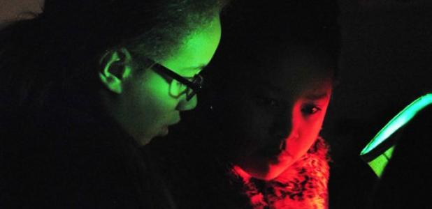 Joelle Spinks and Victoria Ventura, fourth graders at Martin Walker Elementary School, use a black light to search for clues on a piece of paper containing a sentence with comma splices.