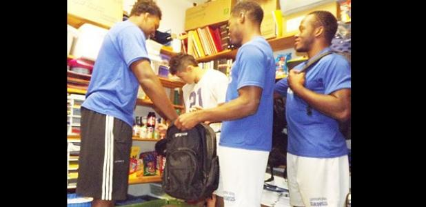 DECA students Michael Sumrall, Andrew Luthner, Jaylen Waters and Breyon Jackson load a backpack with groceries from the group's food pantry for students in need.