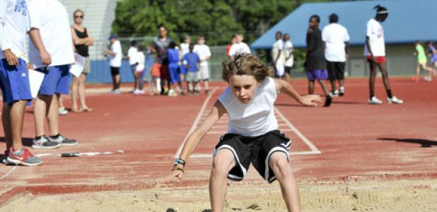 Nick Hooten lands in the sand pit as he competes during a summer track meet at Bulldawg Stadium. The summer track program kicksoff June 9.