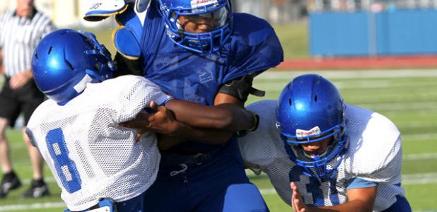 Copperas Cove running back Trent Canion is tackled by defenders Shamad Lomax (8) and Jace Leimbach during the Soap, Shampoo and Towel intrasquad scrimmage on Saturday at Bulldawg Stadium. The team will hit the road for their first scrimmage against another team.