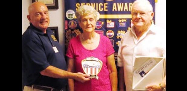 Mark Peterson, left, presents Francis and Rita Walker with the Proudly We Hail award for flying their flag.