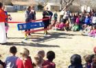 """CCLP/DAVID J HARDIN - Fairview/Miss Jewell Students watch as Principal Leah Miller cuts the ribbon opening the new """"Buddy Bench"""" on the campus Friday afternoon"""
