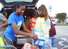 CCLP/LYNETTE SOWELL - DECA Club member Ariana Wilson helps load donated food items after a food drive held at Walmart on Friday. The club collected food for the CCHS weekend food backpack program to help fellow CCHS students in need.