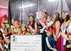 CCLP/BRITTANY FHOLER - The Rabbit Fest Royalty and the newly crowned Krist Kindl Royalty pose with a check with the amount raised for Mitochondrial Disease awareness at the 2nd annual Miss Krist Kindl Charity Pageant held in Bearables in downtown Copperas Cove Saturday morning.