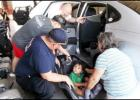 CCLP/PAMELA GRANT -  Firefighter Kris Hurst shows Shirley Anderson how to properly strap her grandson, AJ Zavala, into his new car seat.
