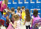 Devin Kasa helps her class find their lockers during the first morning session at Mae Stevens Early Learning Academy.