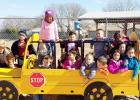 COURTESY PHOTO - Mae Stevens Early Learning Academy students enjoy playing like they driving the car on the school's new playground. Things like shifting gears on a car or scaling a climbing wall develop gross motor skills and require deliberate movement.