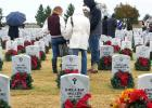 CCLP/FILE ART - Volunteers pause at a grave during last years wreath laying ceremony at the Central Texas State Veterans Cemetery. This year Marty Smith is looking for 300 volunteers to help lay 2,300 wreaths.