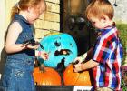 Colin and Isabella Maybury look at their family's Halloween display with teal pumpkins, noting non-food treats available for children with food allergies.