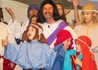 Sid Sharp, center, is surrounded by children as they run through a dress rehearsal of the annual play.
