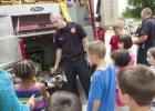 Ethan Westbrook shows the Jaws of Life to a group of young readers as they visit the library for Big Trucks day Tuesday.