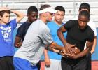 Copperas Cove assistant coach Ryan Youngblood hands off the  all to incoming freshman Miles Alexander as others look on during running back drills on Monday as part of the 2014 Copperas Cove NFL Football Camp at Bulldawg Stadium.