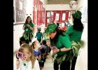 "Williams/Ledger Elementary kindergarten students use their ""leprechaun finders"" which are foam magnifying glasses to hunt for Louie, the leprechaun, and find the pot of gold at the end of the rainbow. – COURTESY PHOTO"