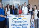 Chamber of Commerce Ambassadors wait with Dr. Daniel Caraveo to cut the ribbon on Benchmark's offices located in the 5 Hills Shopping Plaza. Benchmark moved to the facility in February after practicing in cove for more than five years.