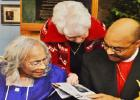 Barbara Burke, one of Alither Mae Stephens' Golden Girl bowling buddies, looks at a newspaper article along with Stephens and Bishop Nathaniel Holcomb.