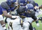 Former Copperas Cove quarterback/receiver Robbie Seybold, center, leads a host of Crusader defenders on a stop of Texas Lutheran's Demetrius Brock during their contest that spanned two days. The Cru won 27-20.