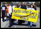 Residents carry the Martin Luther King Jr. banner as they march along FM 116